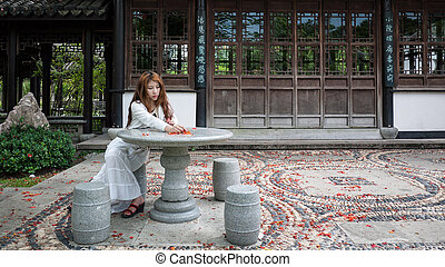Young woman sitting on a chair in the garden Blossoms