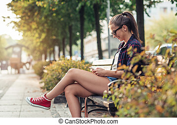 Young woman sitting on a city bench texting