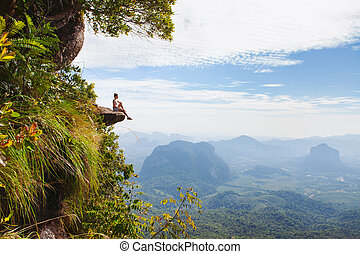 Young woman sitting on a cliff and relaxing.