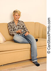 Young woman sitting on a couch watching TV.