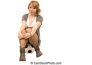 Young woman sitting on a football