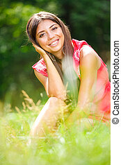 Young woman sitting on a grass