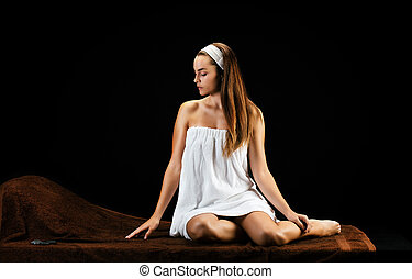 Young woman sitting on a massage bench