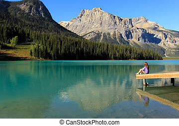 Young woman sitting on a pier at Emerald Lake, Yoho National Park, British Columbia, Canada