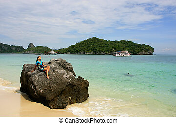 Young woman sitting on a rock at Wua Talab island, Ang Thong National Marine Park, Thailand