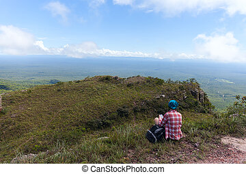 Young woman sitting on a rock with backpack and looking at here mobile phone