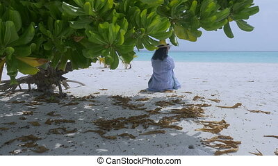 Young woman sitting on a sandy white beach with palm trees in the background.