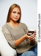 Young woman sitting on a sofa with a cup of hot drink