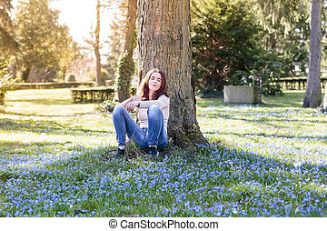 young woman sitting on a spring flower meadow