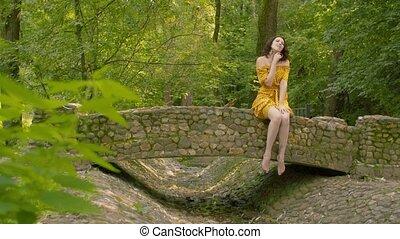 Young woman sitting on a stone bridge