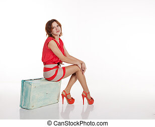 young woman sitting on a suitcase