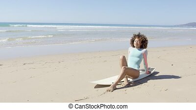 Young woman sitting on a surfboard - Pretty sporty African...