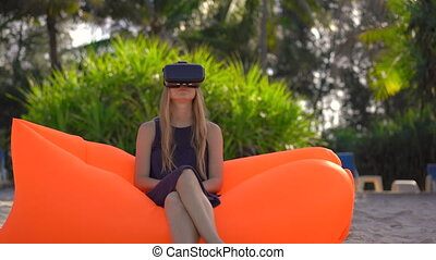 Young woman sitting on an inflatable sofa on a tropical beach uses a VR glasses. Concept of modern technologies that can make you feel like you are somewhere else