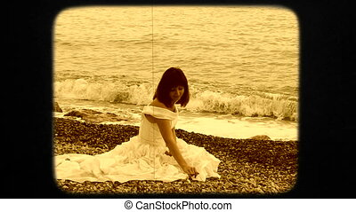 Young Woman Sitting on Beach And Throwing Pebbles Into Black Sea