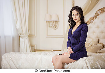 Young woman sitting on bed in bedroom