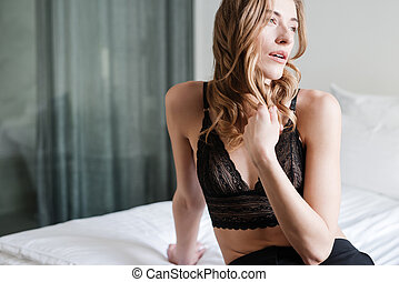 Young woman sitting on bed
