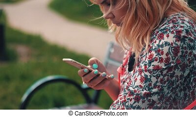Young woman sitting on bench and using smartphone in park. Summer day. Smile