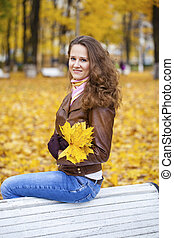 Young woman sitting on bench in the autumn park