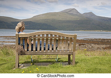 Young Woman sitting on Bench on the Isle of Mull, Scotland