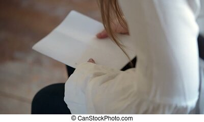 Young woman sitting on chair with documents