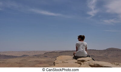 Young woman sitting on cliff's edge and looking at the desert