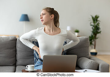 Young woman sitting on couch has a backache