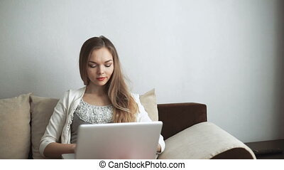 Young woman sitting on couch using laptop and smiling