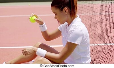 Young Woman Sitting on Court Bouncing Tennis Ball