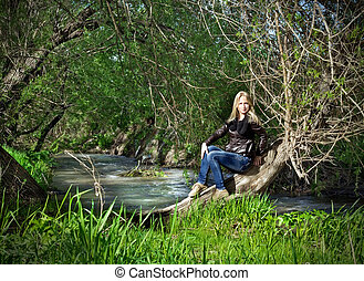 Young woman sitting on dried-up tree