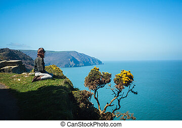 Young woman sitting on edge of cliff - Young woman is ...