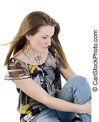 Young woman sitting on floor in jeans and blouse