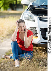 Young woman sitting on ground and leaning on broken car