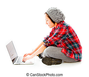 Young woman sitting on ground using laptop