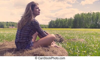 Young woman sitting on haystack at summer