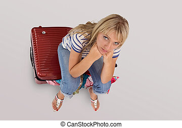 Young woman sitting on her luggage