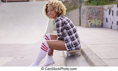 Young woman sitting on her skateboard at the rink
