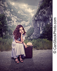 Young woman sitting on her suitcase.