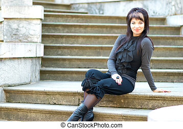Young woman sitting on marble staircase