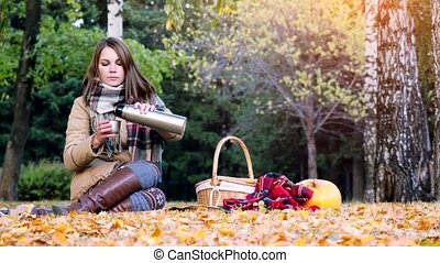Young woman sitting on picnic drinking hot tea from a thermos in autumn park. Girl sitting on the rug near the pumpkin Halloween theme. 3