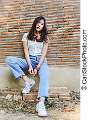 Young woman sitting on red brick wall background.