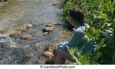Young woman sitting on river shore while summer trekking....