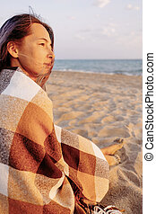 Young woman sitting on sand beach.