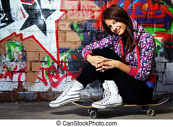 Young woman sitting on skateboard - Young and beautiful girl...