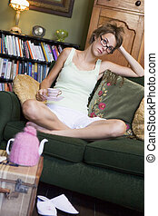 Young woman sitting on sofa at home drinking tea