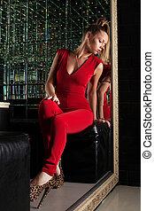 Young woman sitting on sofa in nightclub