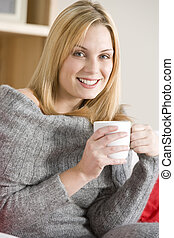 Young Woman Sitting On Sofa With Cup Of Coffee