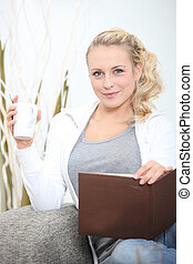 young woman sitting on sofa with photograph album and mug of coffee