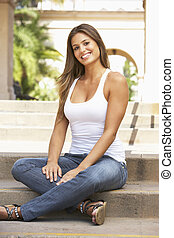 Young Woman Sitting On Steps Of Building