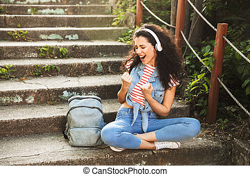 Young woman sitting on steps outdoors