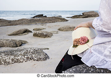 Young woman sitting on stone at beach